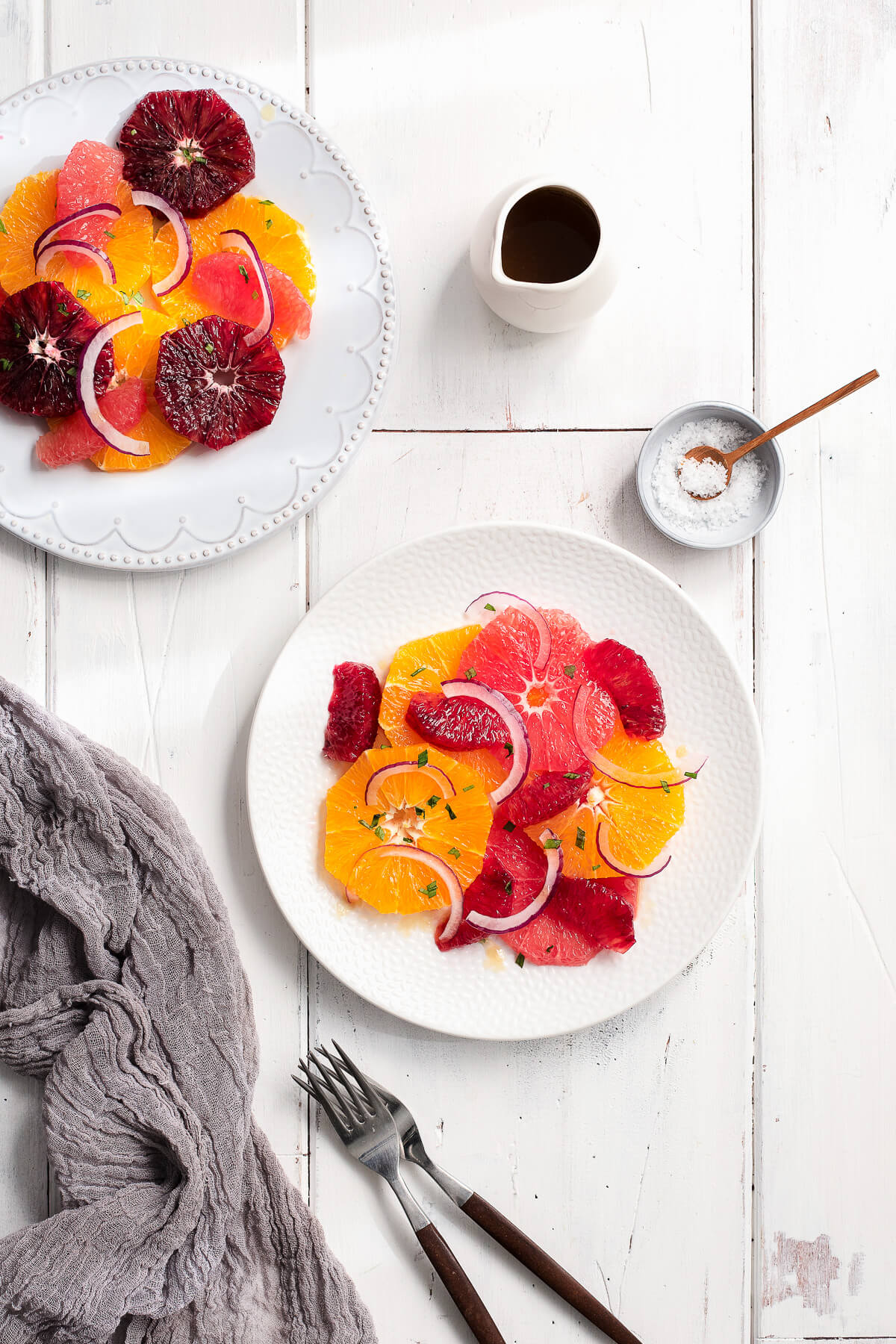 Overhead of two plates of citrus salad with grapefruit, navel oranges, and blood oranges.