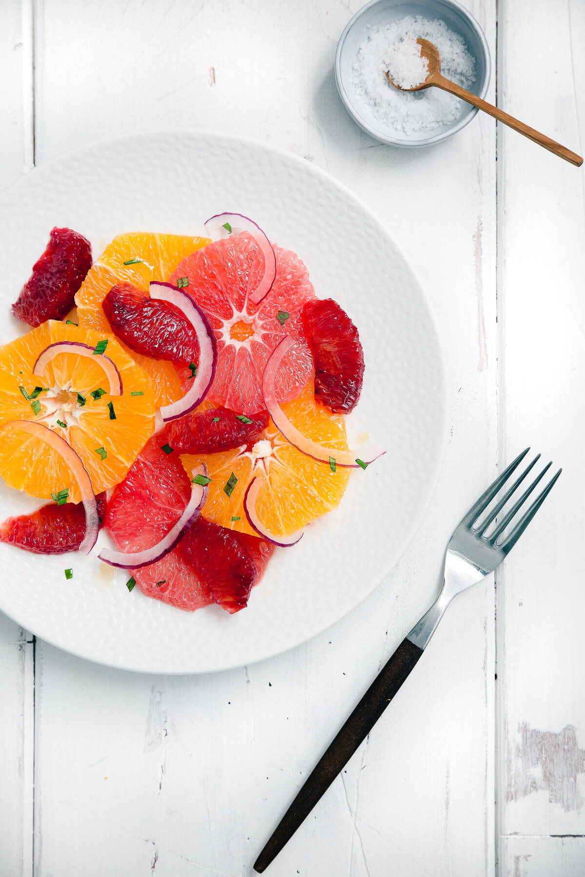 Overhead shot of a citrus salad with grapefruit, blood oranges, and navel oranges on a white plate.