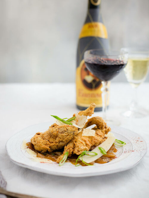 Fried quail on a white plate next to two glasses of wine.