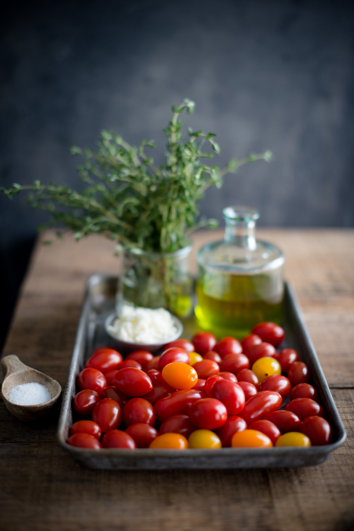 Ingredients for roasted tomatoes set out on a metal tray - tomatoes, olive oil, fresh thyme, feta, and kosher salt.