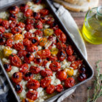 A baking tray of roasted tomatoes and feta topped with olive oil and thyme.