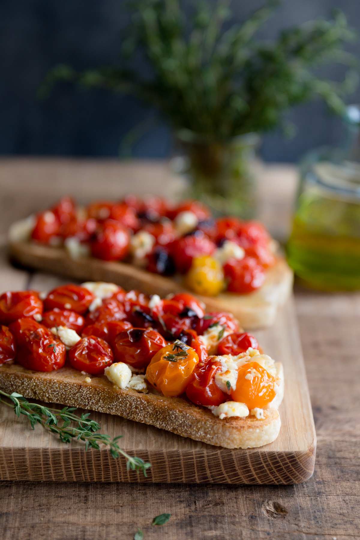 Roasted tomatoes and feta on slices of toasted bread.