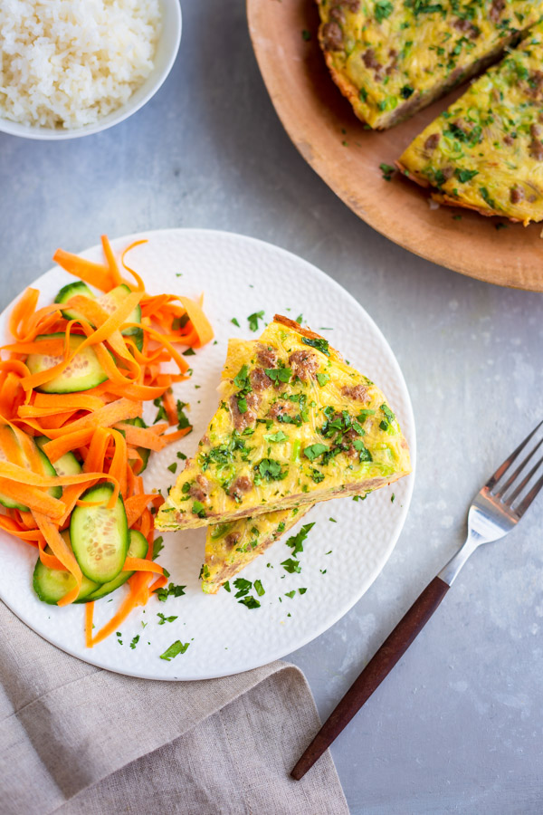 Slices of Vietnamese egg quiche on a white plate with some a cucumber and carrot salad.