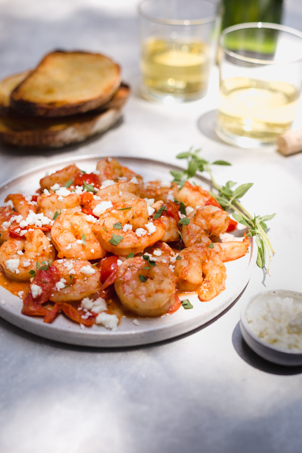 A plate of garlic shrimp on a table outside with glasses of wine.