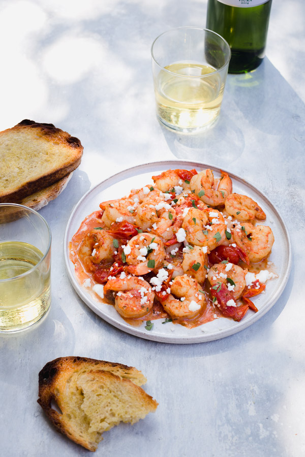 A plate of garlic shrimp with glasses of wine, some feta, and toasted bread.