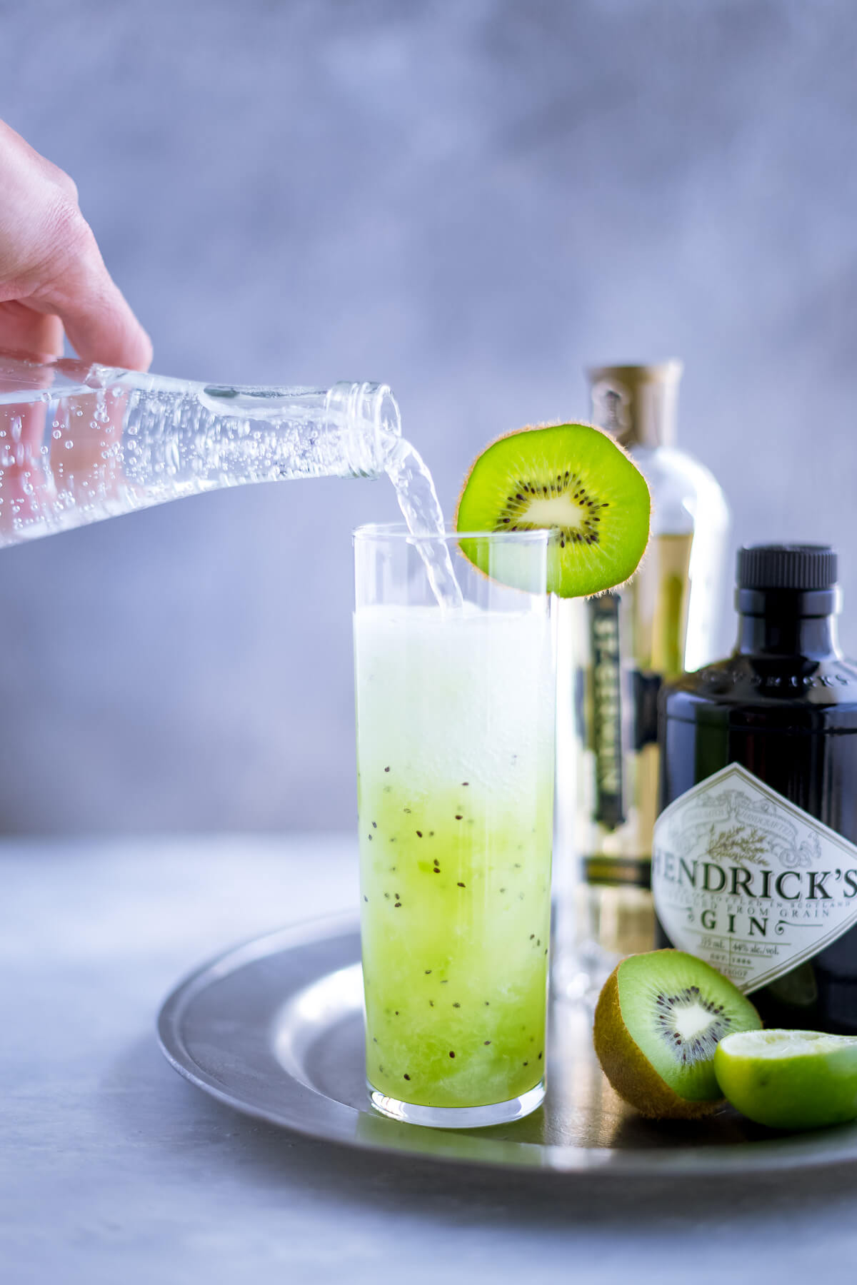 Sparkling water being poured into a kiwi cocktail.
