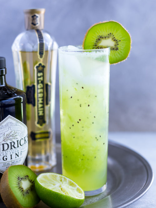 Kiwi cocktail in a tall garnished with a fresh kiwi slice.