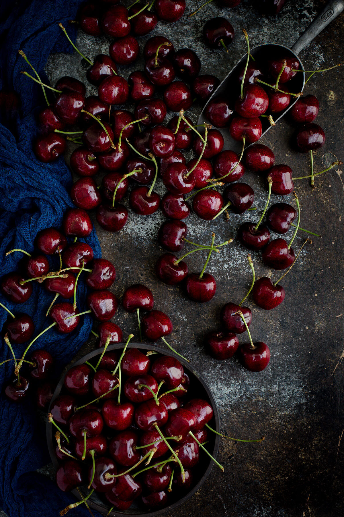 Fresh cherries scattered on a wooden board.
