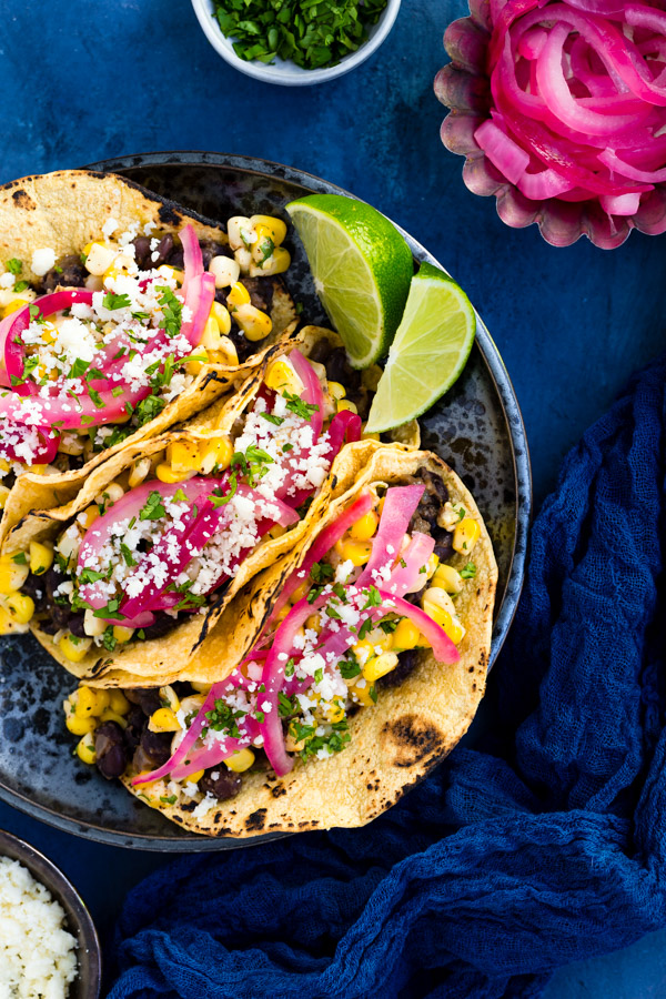 Cuban-Style Black Bean and Elote Tacos - Mexican corn salad and Cuban-style black beans come together in these quick and easy vegetarian tacos. | tamingofthespoon.com
