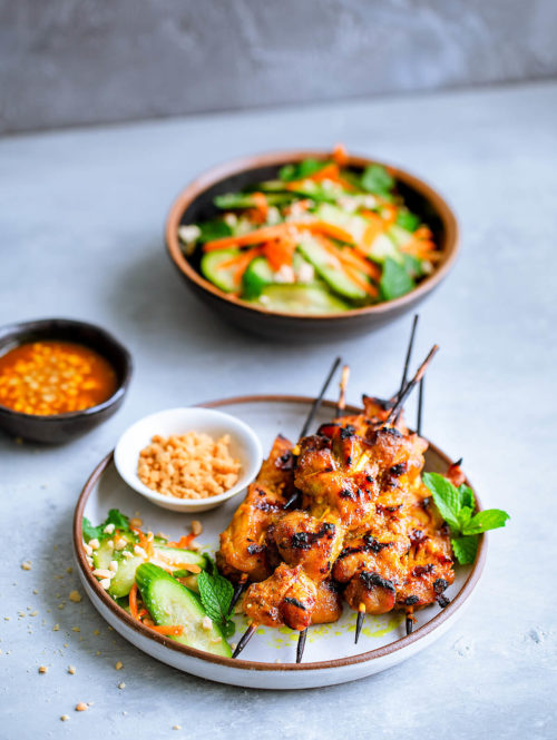 Skewers of chicken satay served with a cucumber salad.