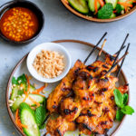 Overhead view of skewers of chicken satay served with a cucumber salad.