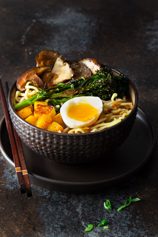 A bowl of miso ramen with roasted mushrooms, butternut squash, and broccolini topped with a soft boiled egg.