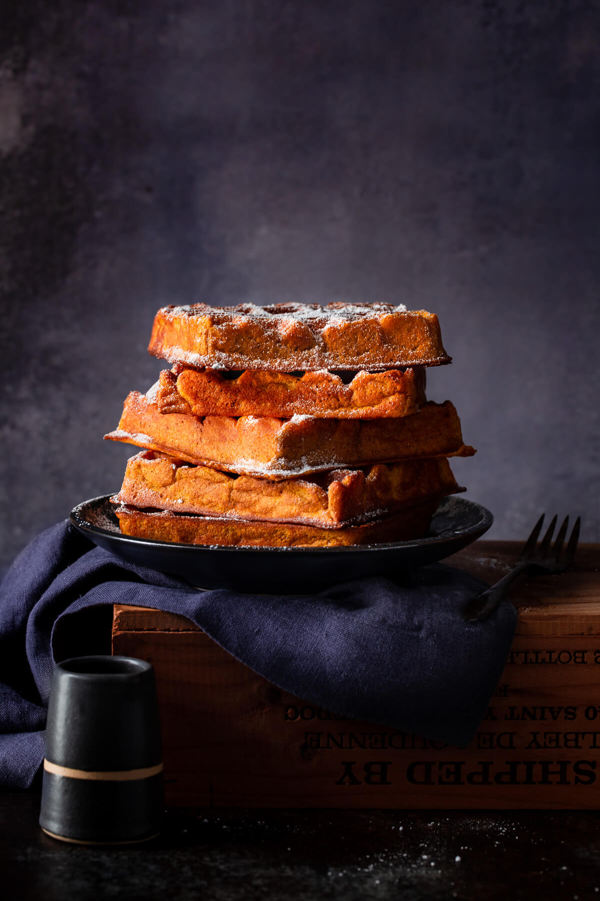 A stack of pumpkin spice waffles on plate on a wooden box.