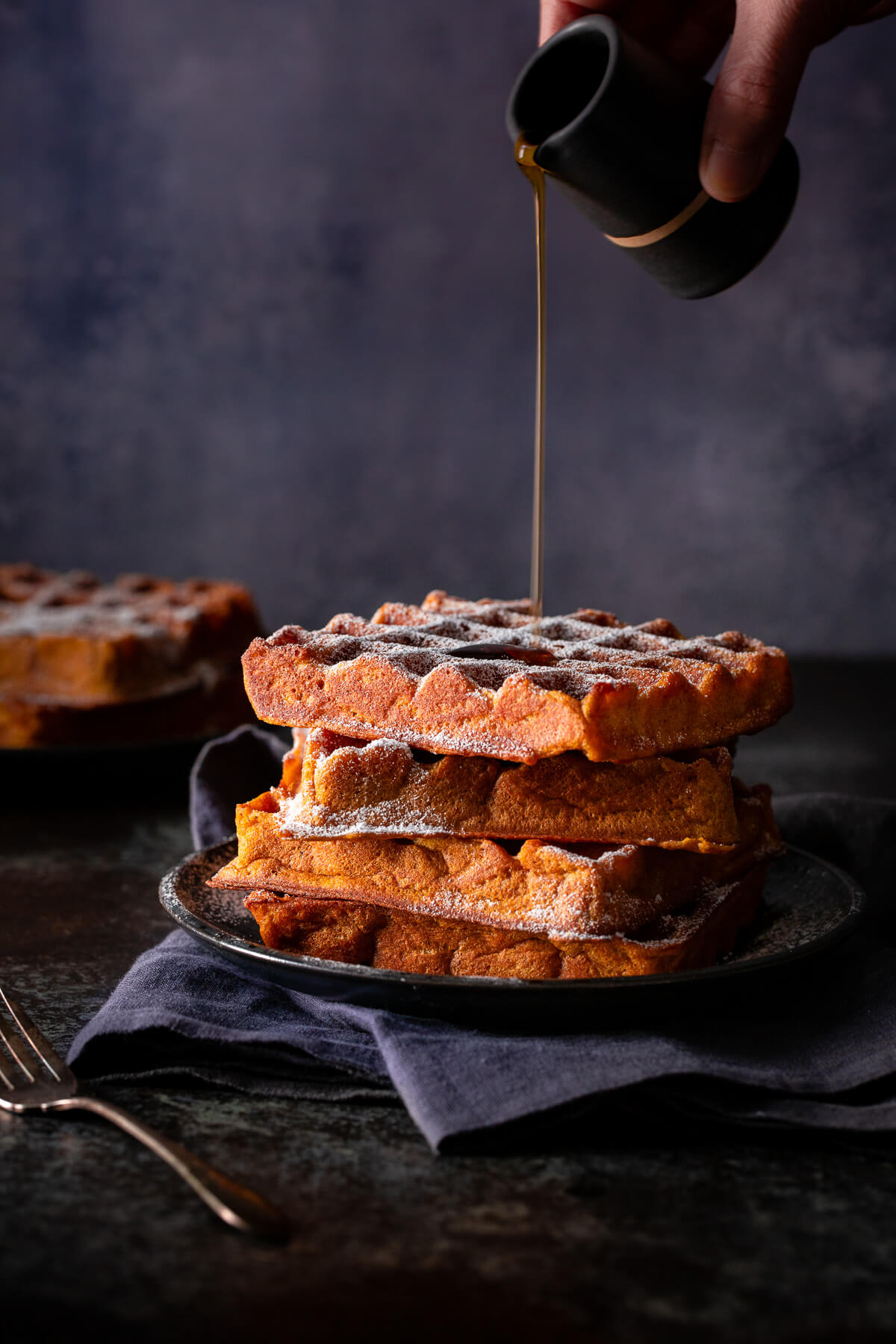 Syrup being poured on a stack of pumpkin spice waffles.