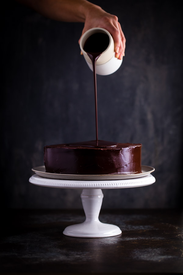 Chocolate ganache being poured on an inside-out German chocolate cake.