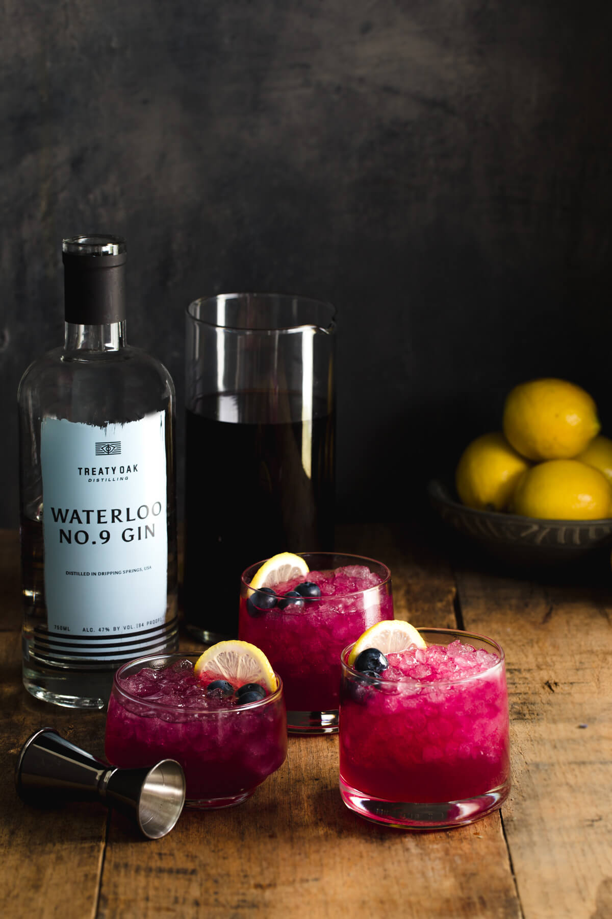 Three glasses of gin cocktail with lemon juice and blueberry-lavender-juniper simple syrup next to a bottle of gin and a jigger.