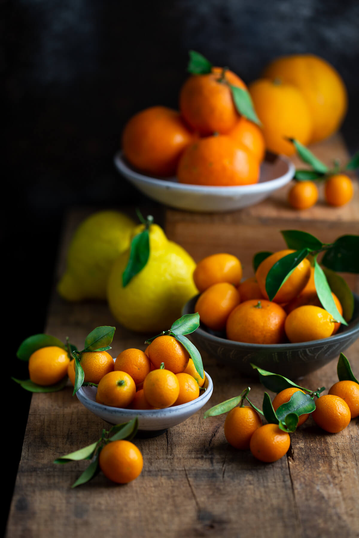 Several bowls of citrus on a wooden tabletop.
