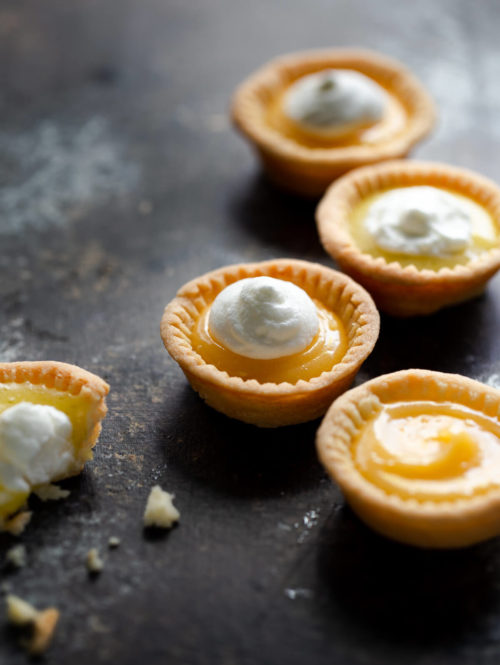 Close-up of several lemon tartlets topped with whipped cream on a tabletop.