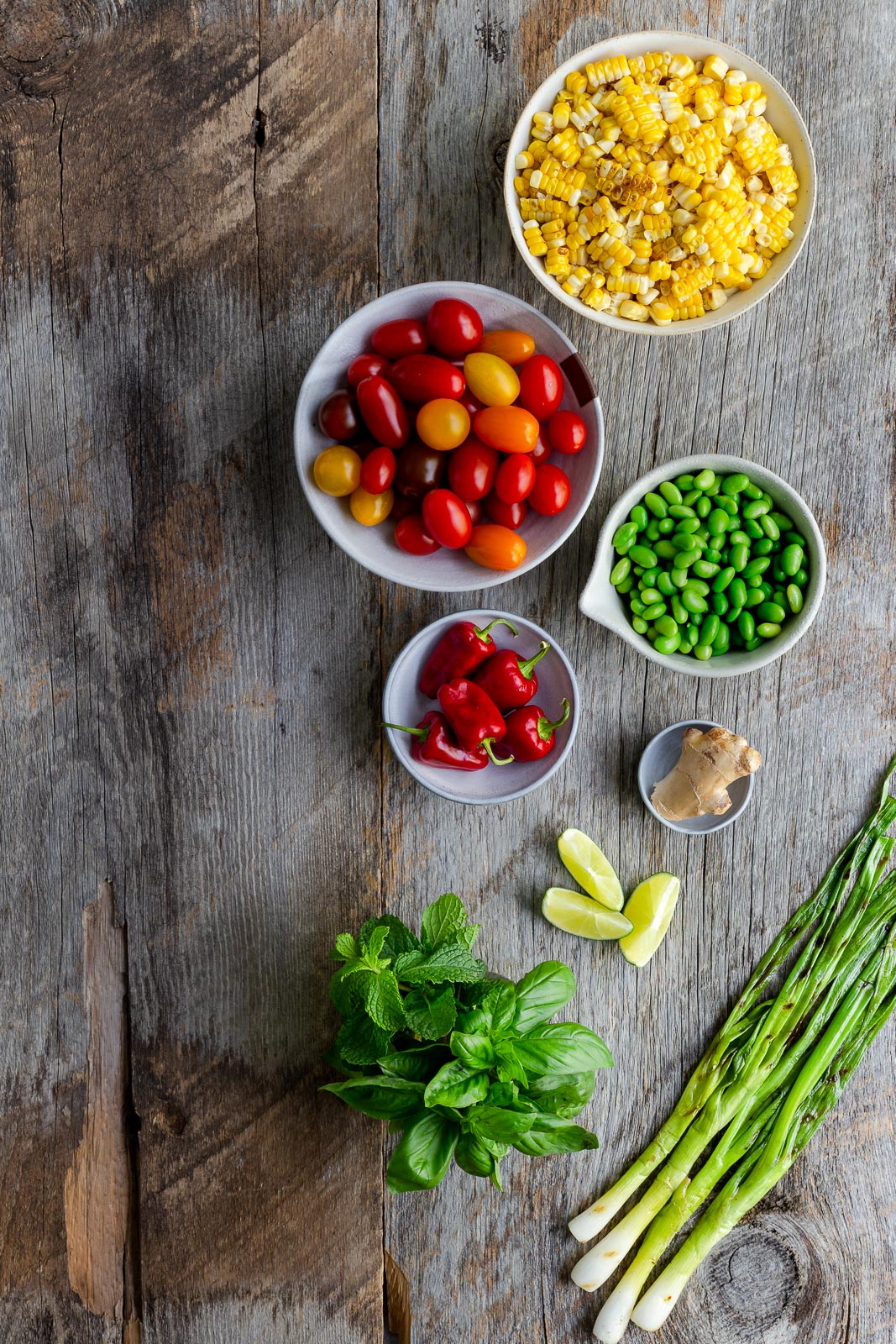 Ingredients for making corn salad on a wooden tabletop.