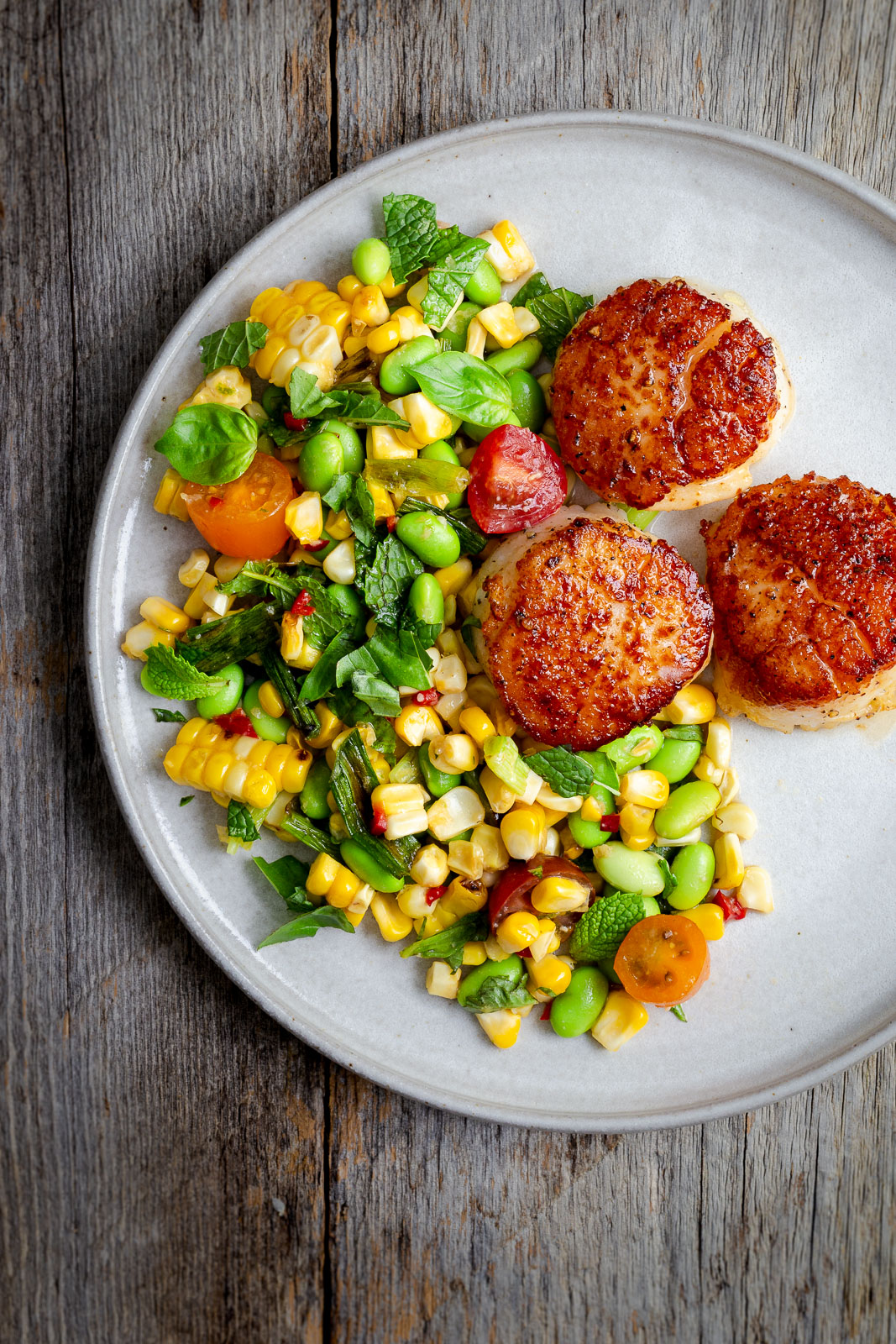 Three seared scallops and a salad of corn, tomatoes, edamame, and chopped herbs on a gray plate.