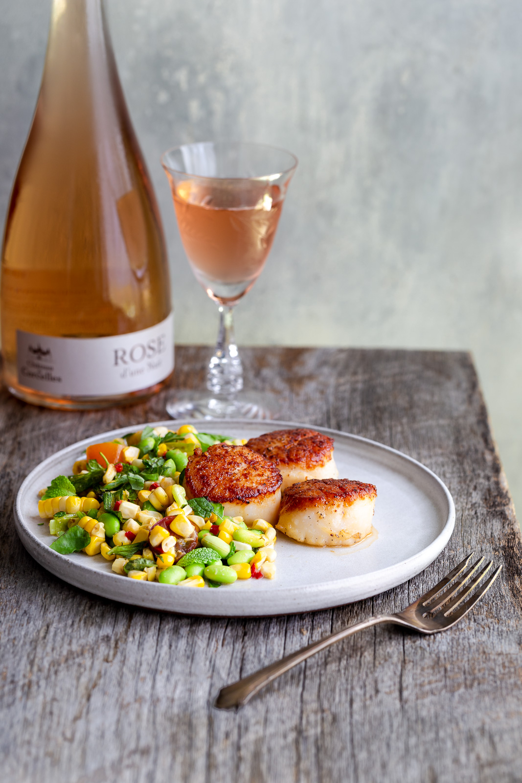 A plate of seared scallops and corn salad next to a glass of wine.
