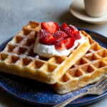 Two Belgian waffles topped with whipped cream and strawberries on a blue plate.