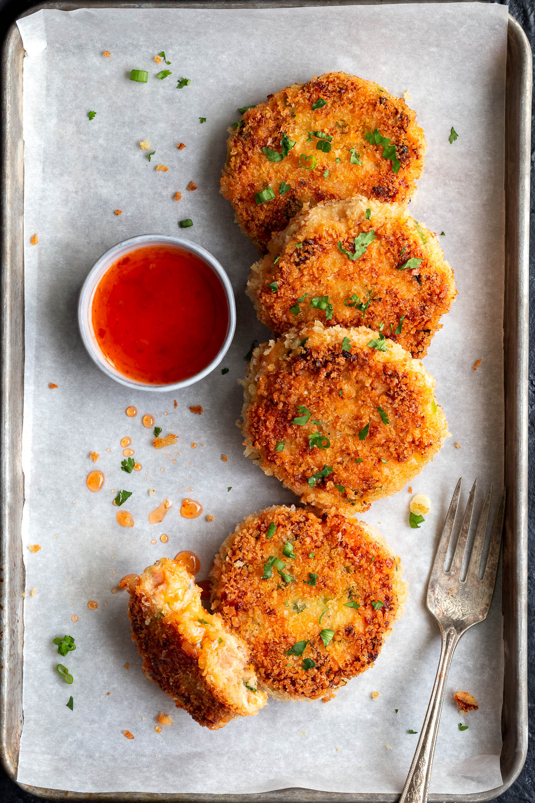 Top view of some salmon cakes served with sweet chili sauce.