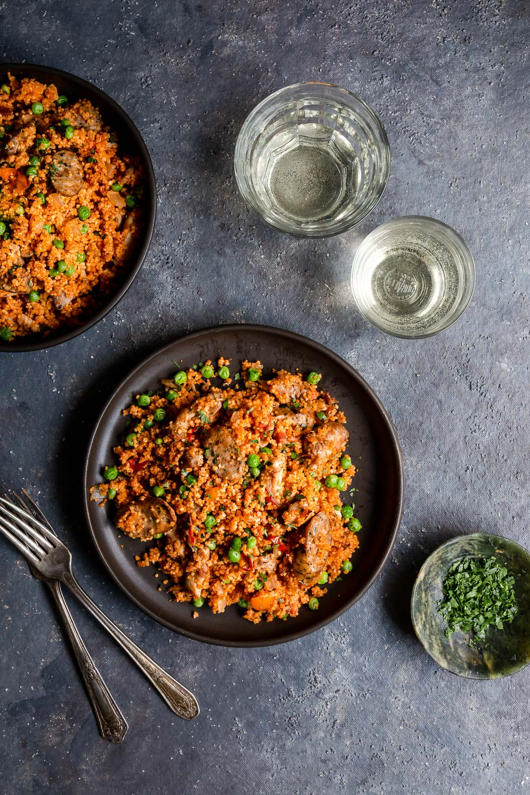 Overhead view of chicken and sausage couscous paella  on a brown plates with glasses of white wine.