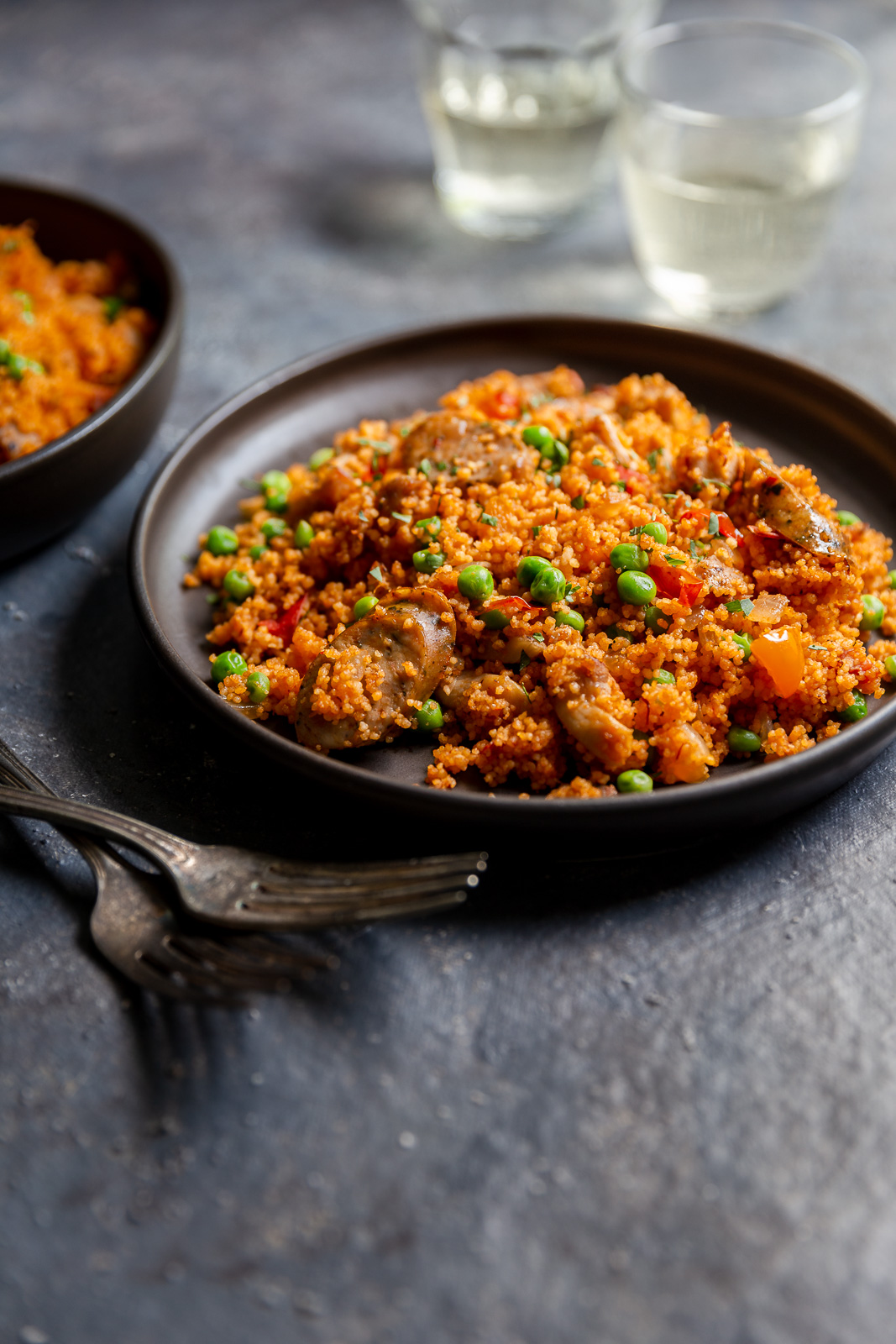 Chicken and sausage couscous paella  on a brown plate with glasses of white wine.
