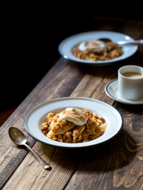 Two plates of breakfast apple crisp and a cup of coffee on a wooden table.