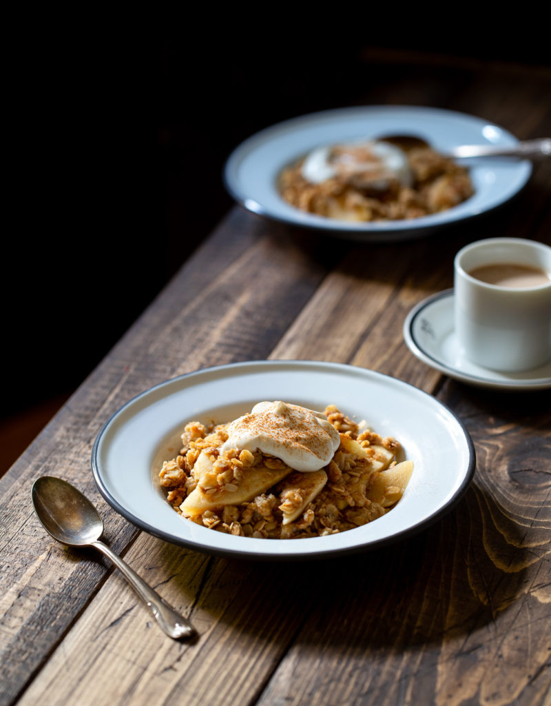 Two bowls of apple crisp with a crunchy oat topping and a dollop of Greek yogurt.
