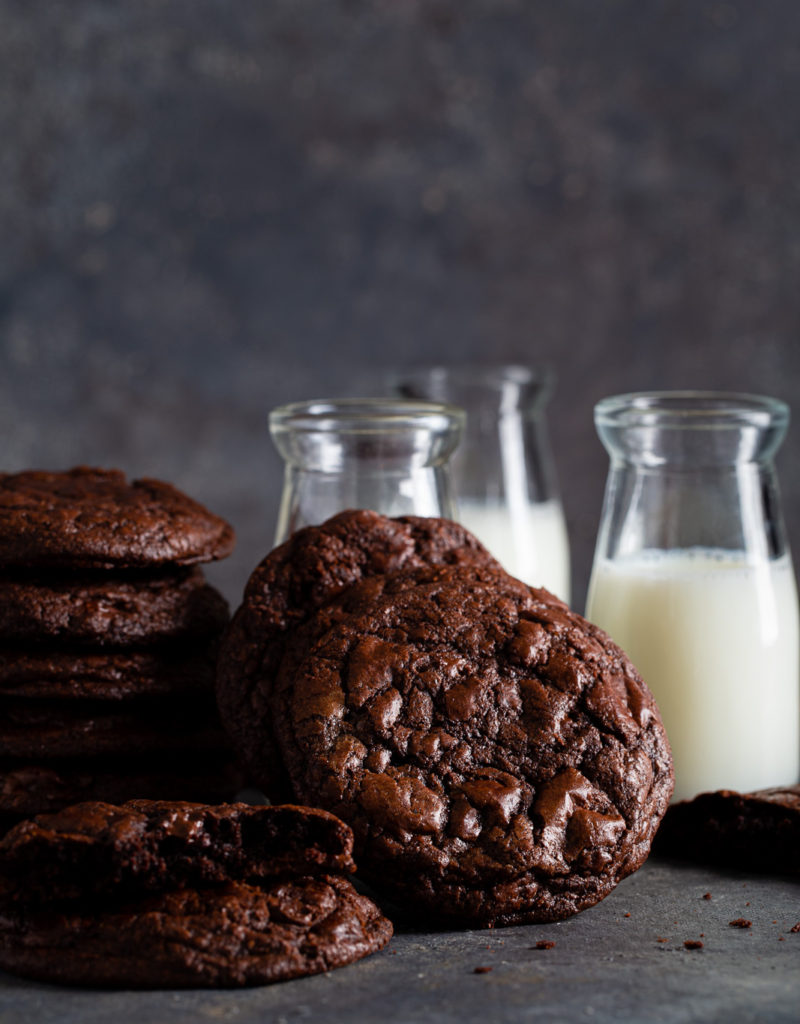 Stack of dark chocolate cookies shown with small bottles of milk.