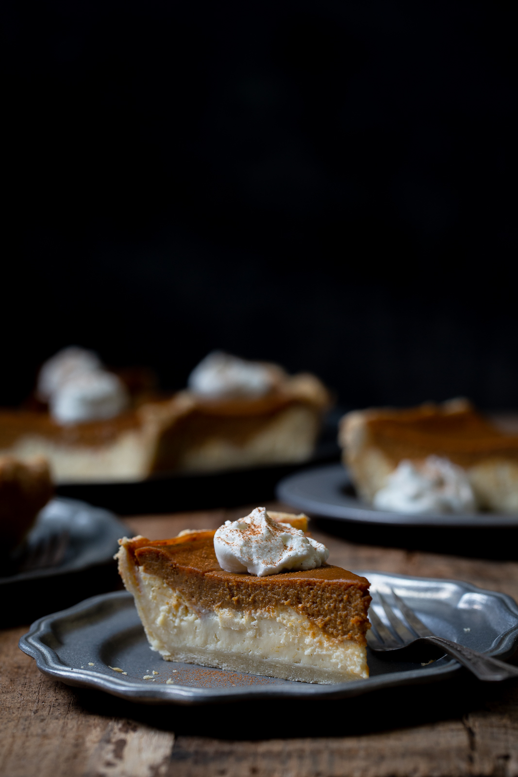 Slice of layered pumpkin cheesecake pie on pewter plate on wooden board with more pie slices in the background.