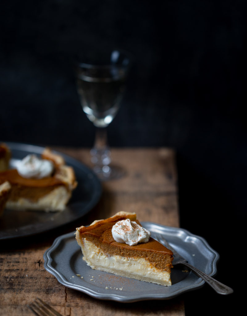 Slice of layered pumpkin cheesecake pie on pewter plate on wooden board with more pie slices and glass of white wine in the background.