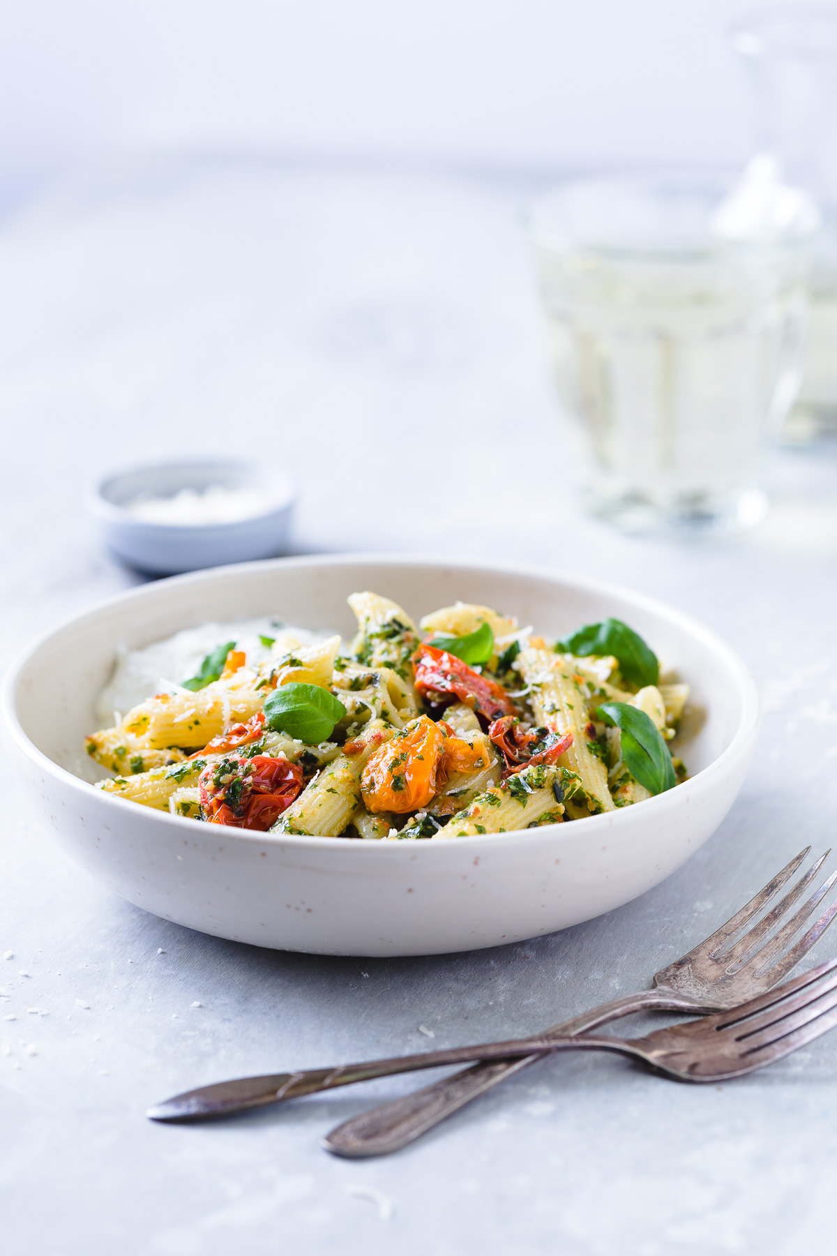 Penne tossed with kale pesto and roasted tomatoes and a serving of burrata cheese in a white bowl.