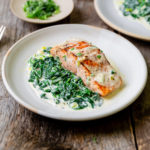 Close-up of pan seared salmon with creamed spinach on the side.