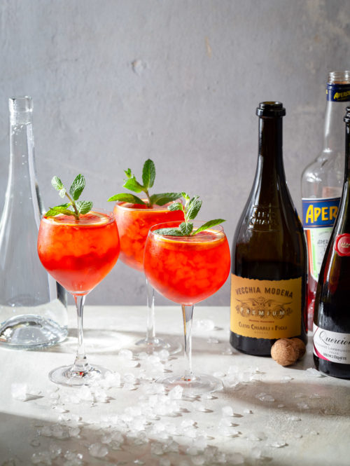 Three Lambrusco spritz cocktails garnished with orange slices and mint sprigs.