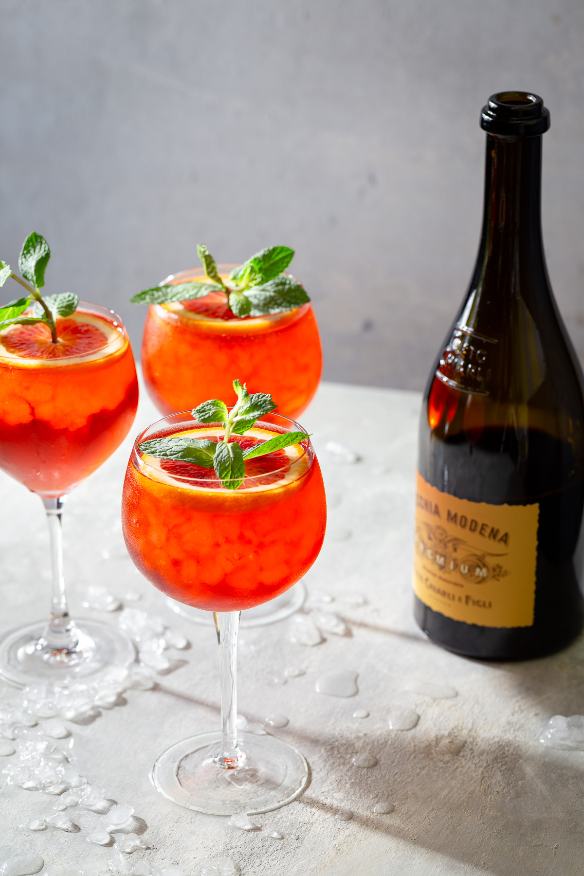 Three Lambrusco spritz cocktails in wine glasses and garnished with orange slices and mint sprigs shown with a bottle of Lambrusco.