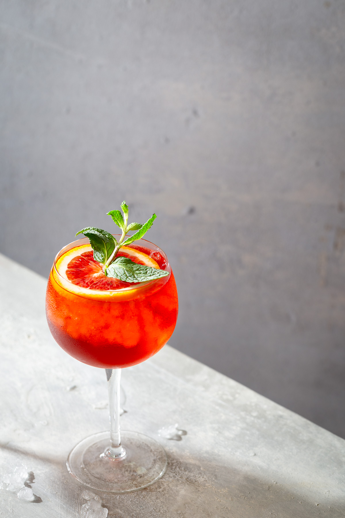 Lambrusco spritz cocktail in a wine glass and garnished with orange slices and mint sprigs.