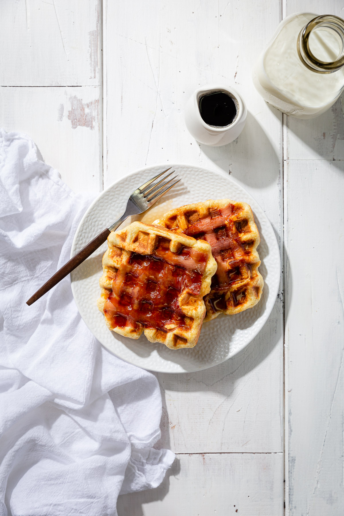Prosciutto waffles on a white plate with a small pitcher of syrup, a bottle of milk, and white napkin.