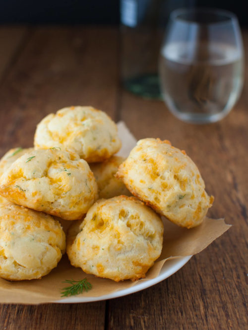 Plate of cheddar dill puffs on a wooden background.