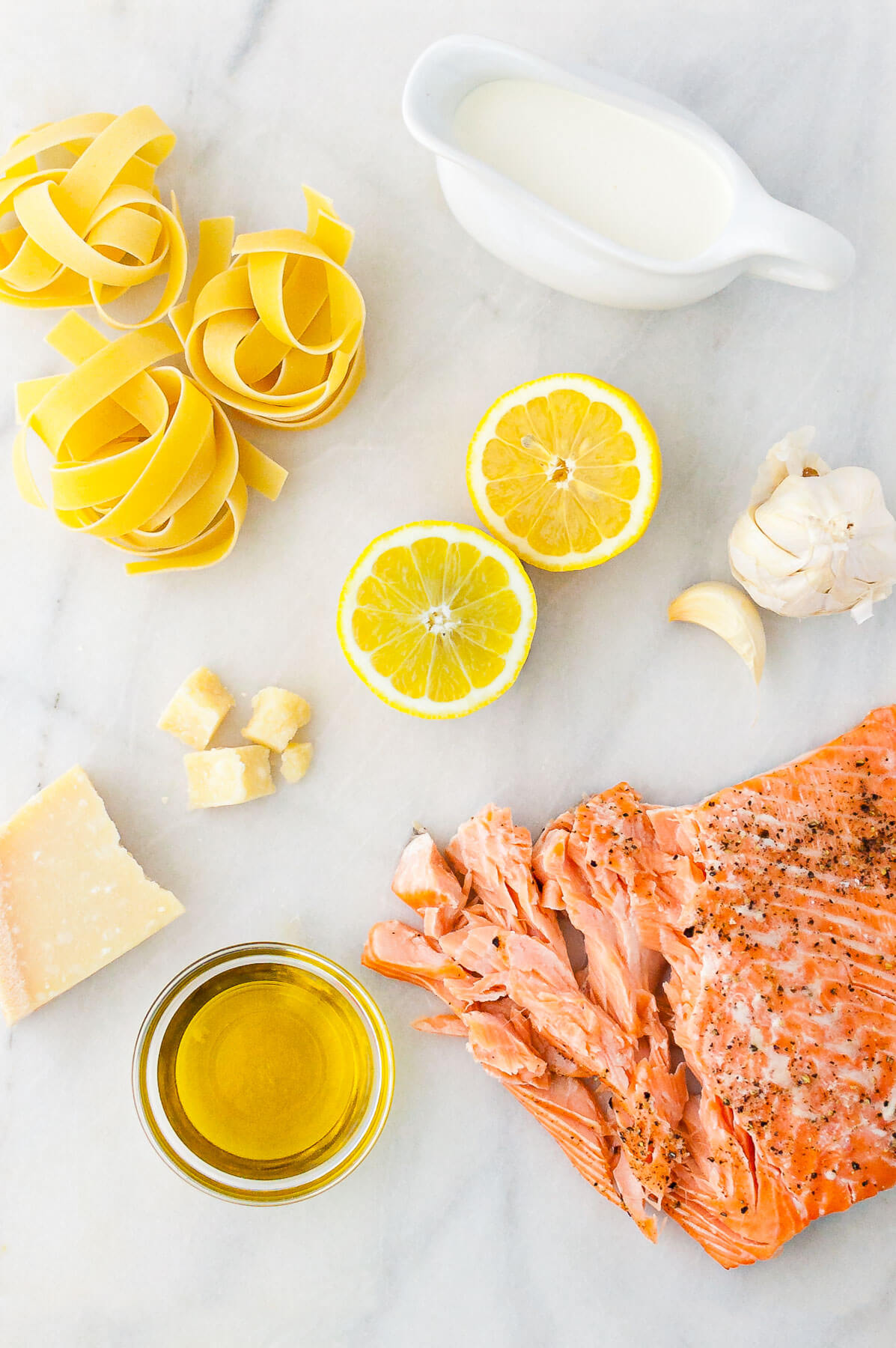 Ingredients for lemon pasta with salmon - dried pappardelle, cream, parmesan cheese, lemon, garlic, olive oil, and roasted salmon.