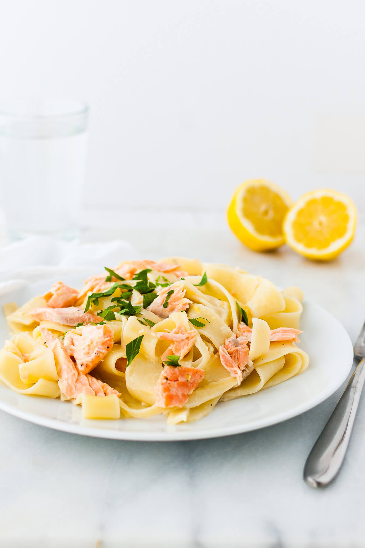 Lemon pasta with salmon garnished with chopped parsley on a white plate.