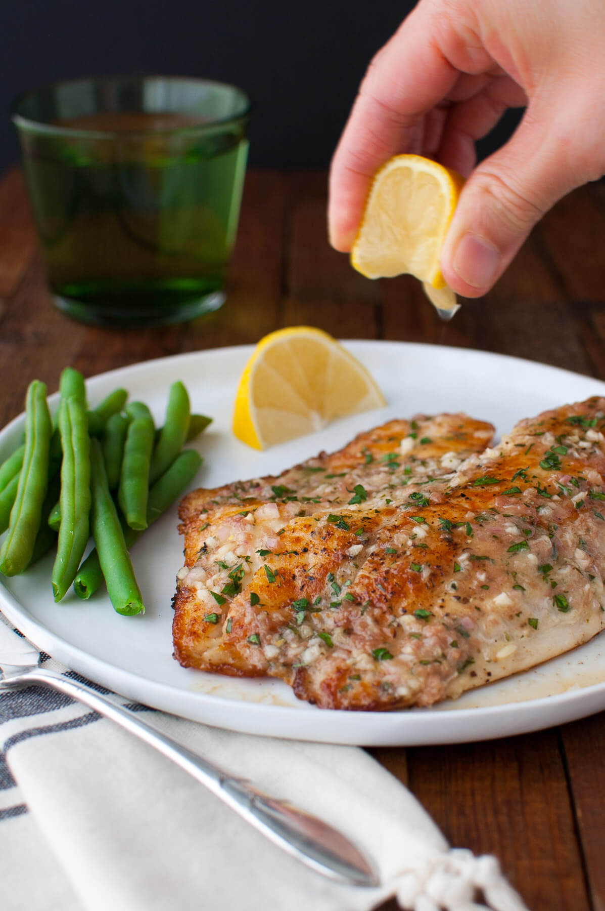 Fresh lemon juice being squeezed on a sautéed tilapia fillet with green beans and lemon wedges on a white plate.