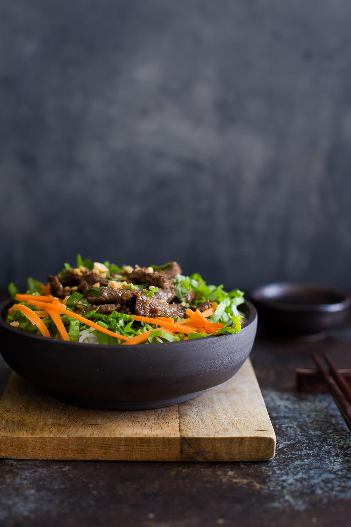Bowl of Vietnamese lemongrass beef with noodles, lettuce, and shredded carrots.