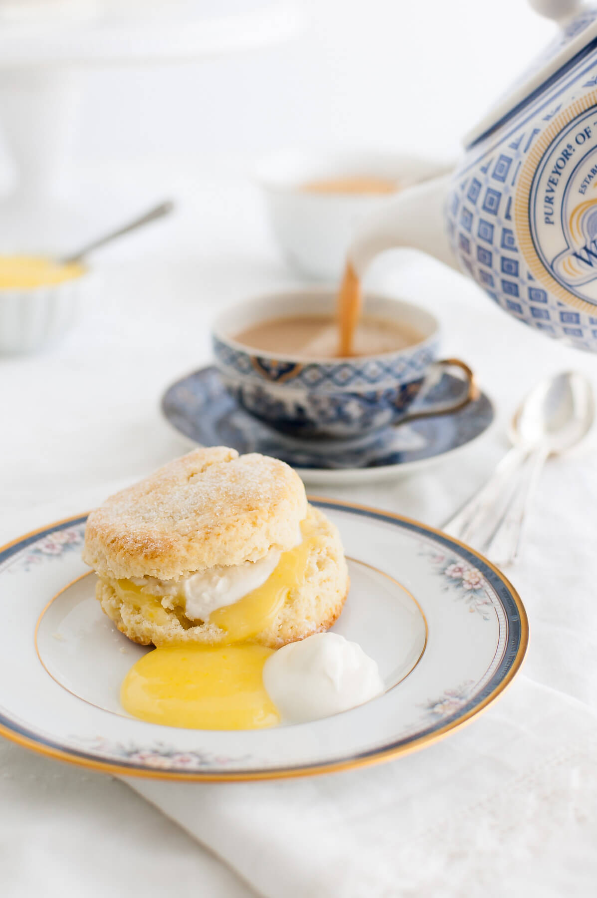 Cream scone, lemon curd, and whipped cream on a china plate with a cup of tea being poured in the background.