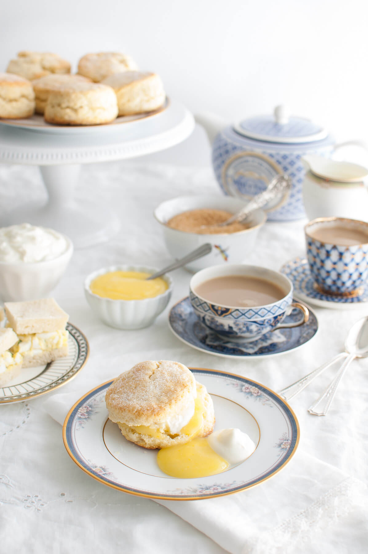 A table set for afternoon tea with scones, lemon curd, whipped cream, tea sandwiches, and cups of tea.