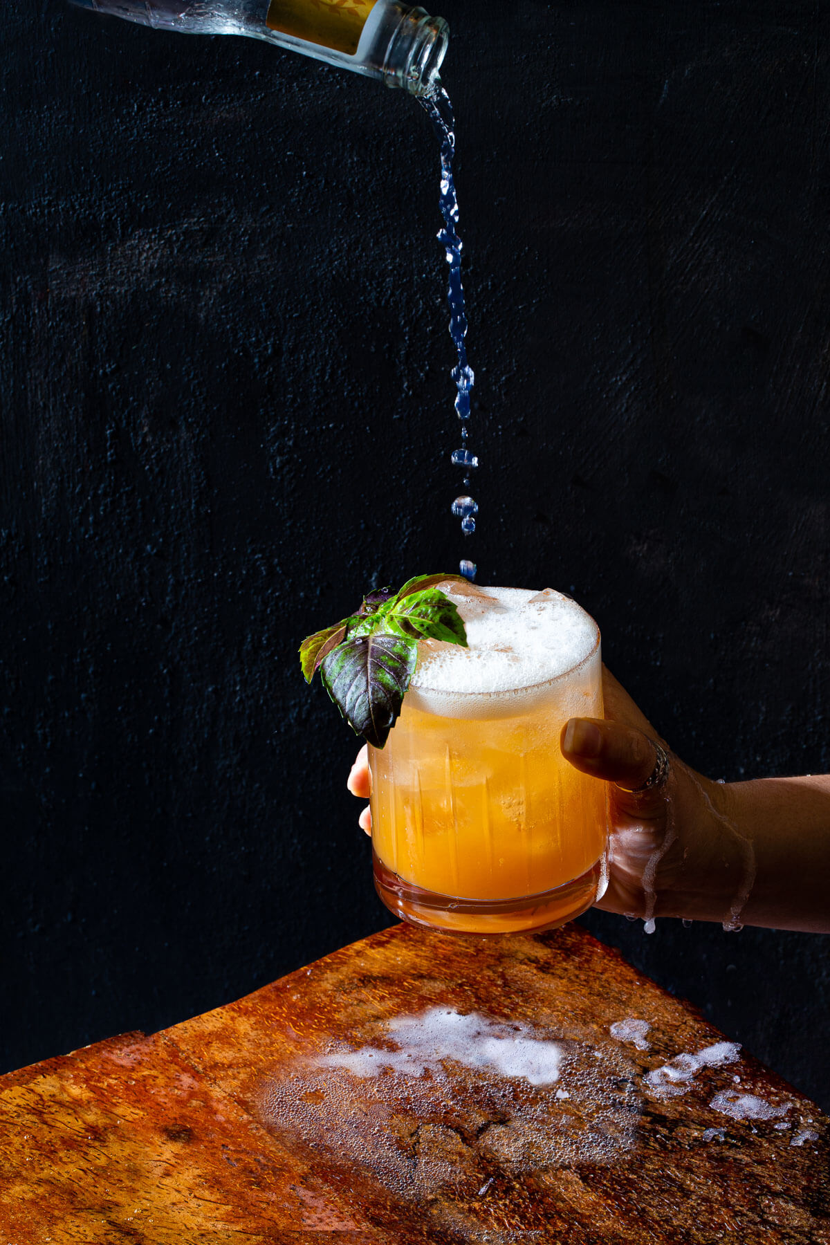 A hand holding a glass filled with a peach-basil gin shrub cocktail while tonic water is poured into.