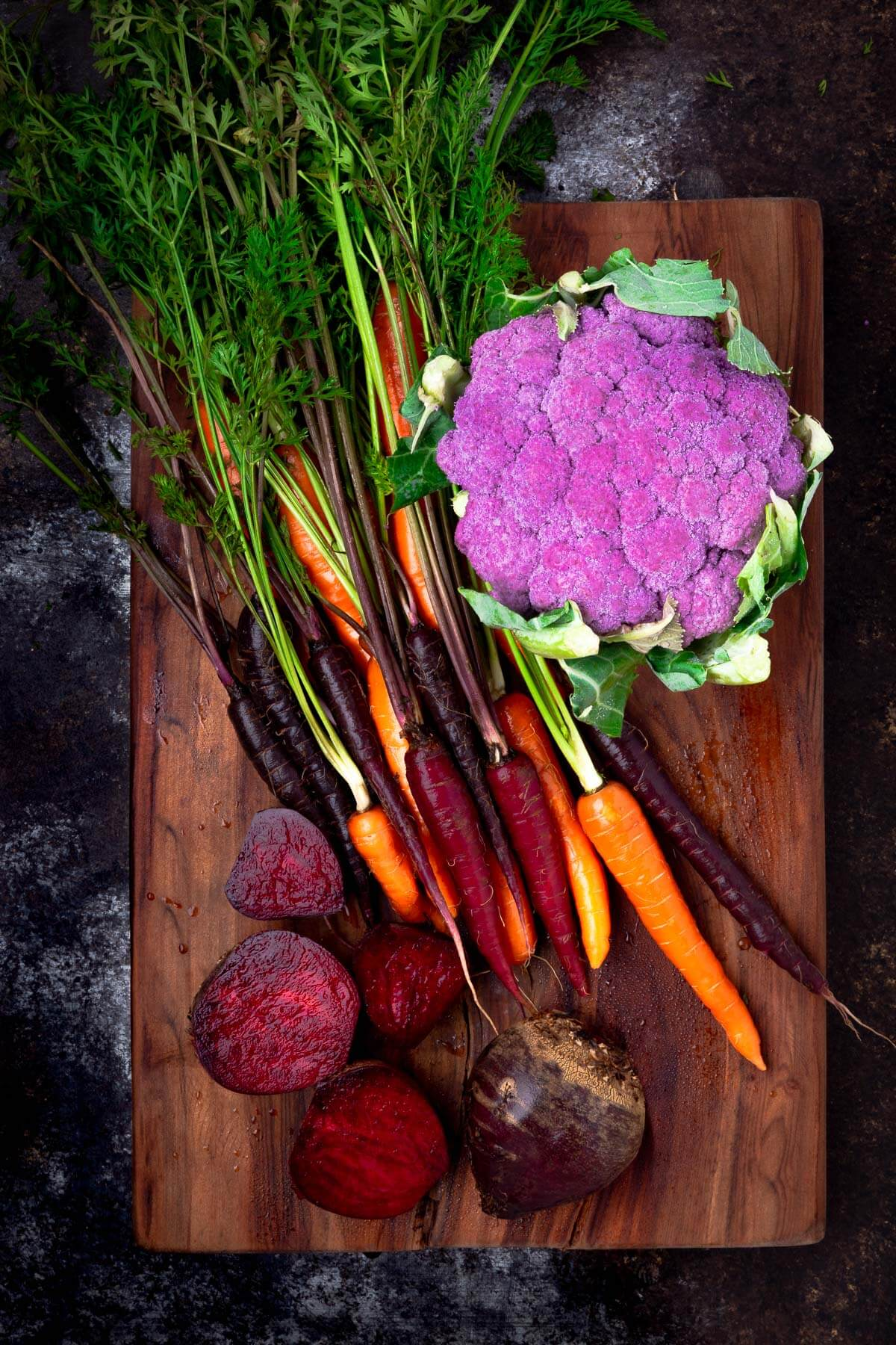 Fresh rainbow carrots, purple cauliflower, and beets on a wooden cutting board.