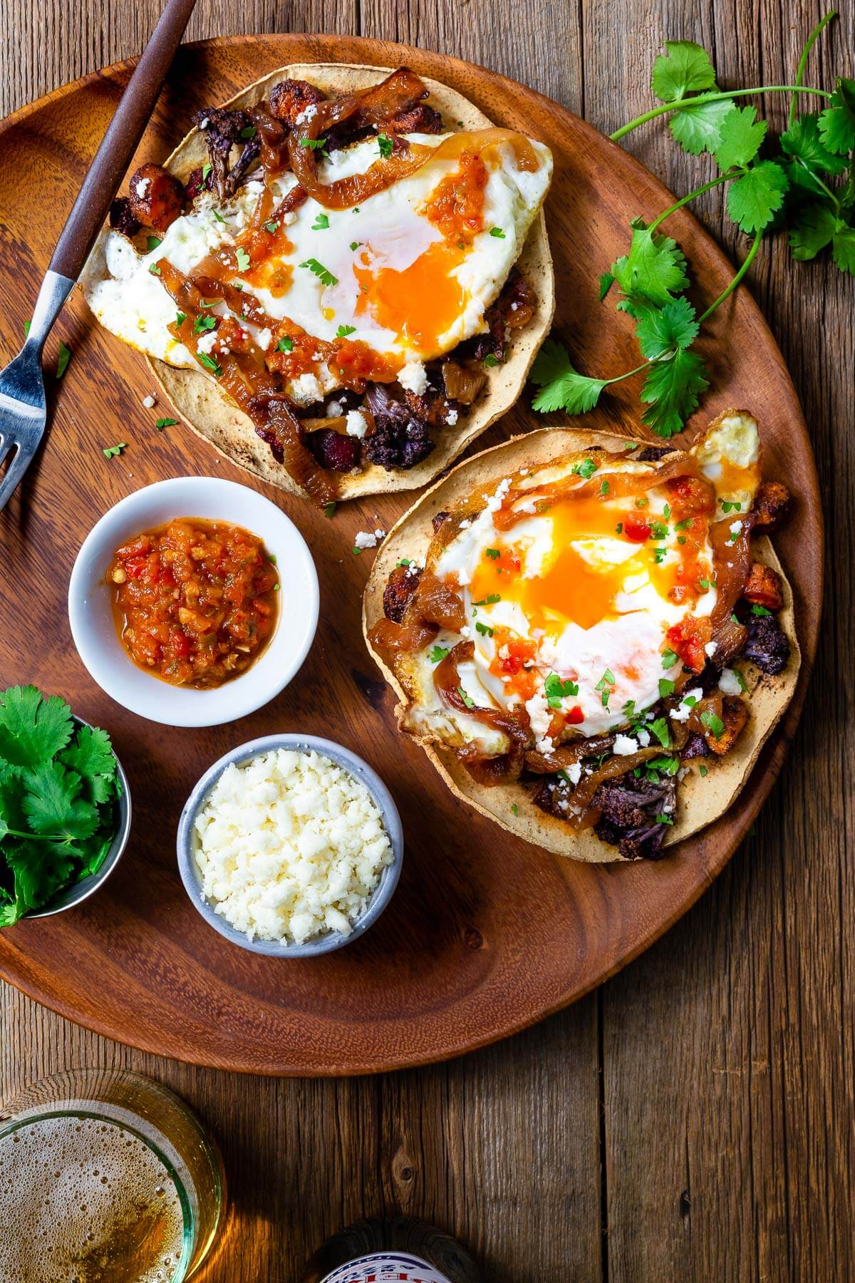 Roasted vegetable tostadas with fried eggs on a wooden plate with small bowls of salsa, crumbled cheese, and cilantro.